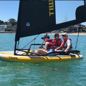 Dad sailing the Tiwal 3 inflatable sailboat with his two kids